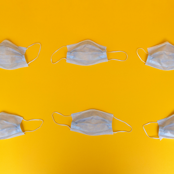 Row of white face masks on yellow background