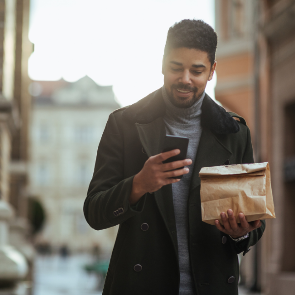 Dark skinned man in winter coat walking while holding lunch bag and looking at smart phone