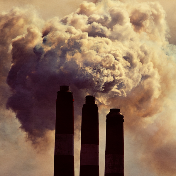 Photo of polluted sky with chimneys in diminishing heights in foreground